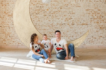 Happy family father, mother and child son near a blank brick wall in the room.