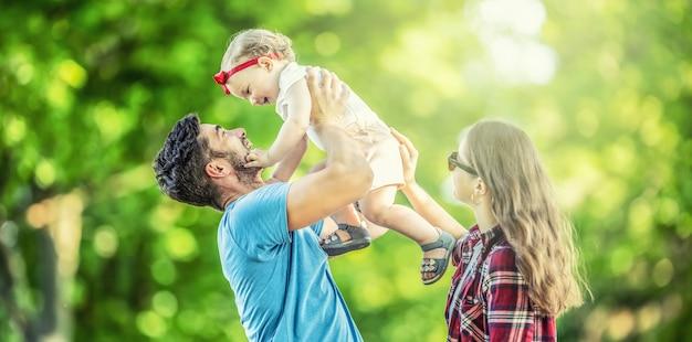 幸せな家族、父、母、娘が公園で遊んでいて、晴れた夏の日を楽しんでいます。