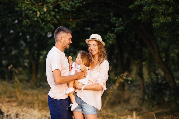 행복한 가족. 아버지, 어머니와 딸이 공원에서
