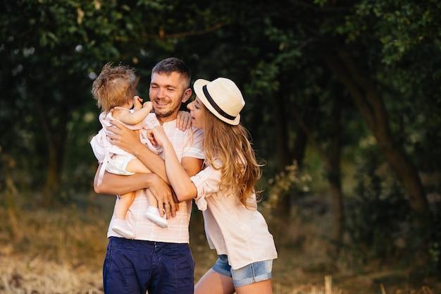 Счастливая семья. отец, мать и дочь в парке