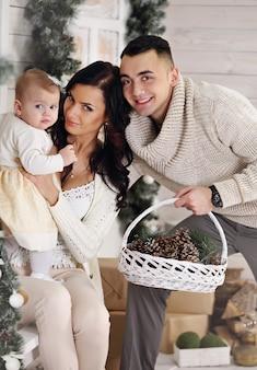 Счастливая семья, отец, мать и дочь на крыльце с рождественскими украшениями