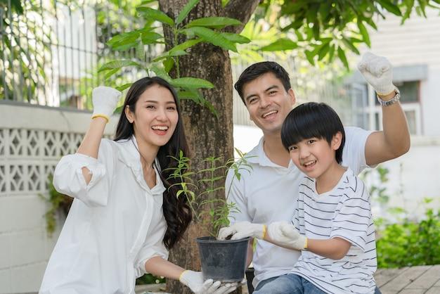 행복한 가족 아버지 어머니와 아들은 집에서 정원에 나무를 심는 것을 돕습니다.