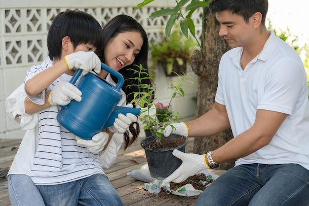 행복한 가족 아버지 어머니와 아들은 집에서 정원에 있는 나무에 물을 주는 것을 함께 돕습니다.