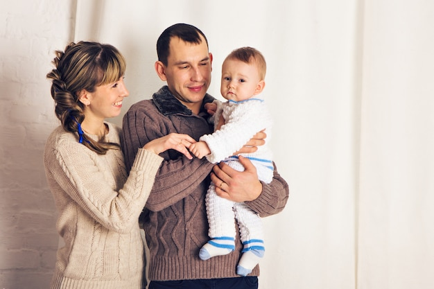 Happy family father, mother and baby boy playing together at home