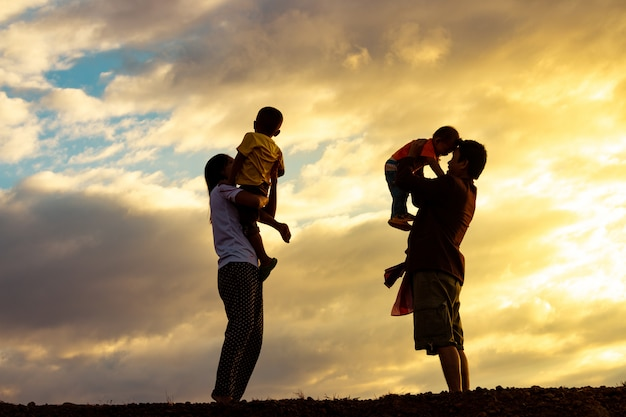 Happy family father, mother and child on nature at sunset.