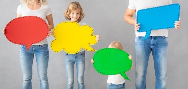 幸せな家族-父、母、娘、息子-カラフルな紙の吹き出しを空白で保持
