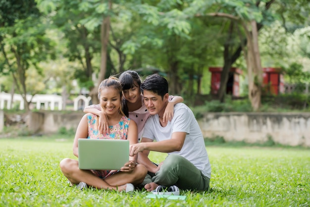 Happy family father, mother and daughter sitting on the grass and playing laptop at outdoor park