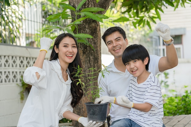 Happy family father mother and son help together plant a tree in garden at homeactivity on holiday