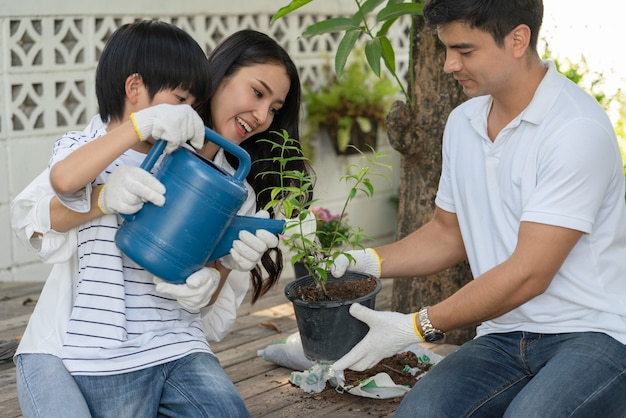 Happy family father mother and son help together watering plant a tree in garden at home