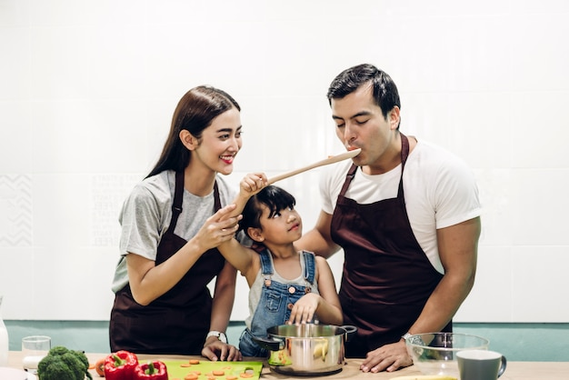 Happy family father and mother with daughter cooking and preparing meal together in the kitchen