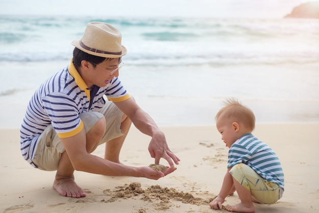 Happy family. father playing sand with cute smiling little asian baby boy child on white sand beach on nature outdoor,