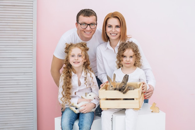 행복한 가족 아버지 두 딸과 푹신한 동물 미소와 함께 아름다운 토끼