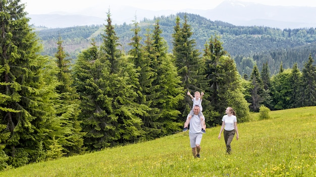 Happy family: father with son on shoulders and mother walking on a green field against the coniferous forest and mountains.