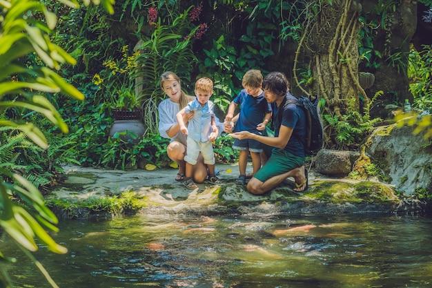 熱帯の池でカラフルなナマズを養う幸せな家族
