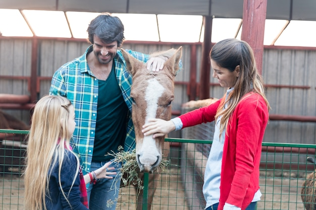 Happy family feeding a horse in the stable