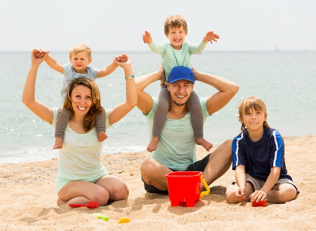Happy family of five smiling at sea beach