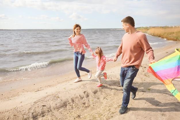 川の近くで凧を飛んで幸せな家族