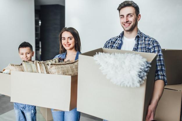 Una famiglia felice di quattro persone porta scatole che entrano nella nuova casa, genitori impressionati e figli portano pacchi di cartone che si trasferiscono nel proprio appartamento,