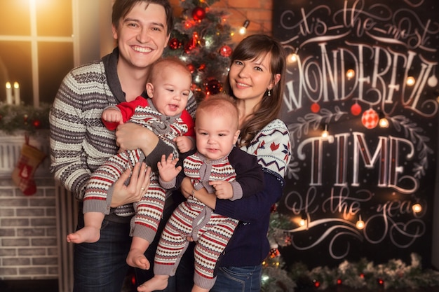 Happy family of four  mom dad and babies twins smiling together christmas