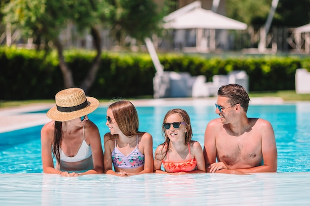 Happy family of four at outdoors swimming pool