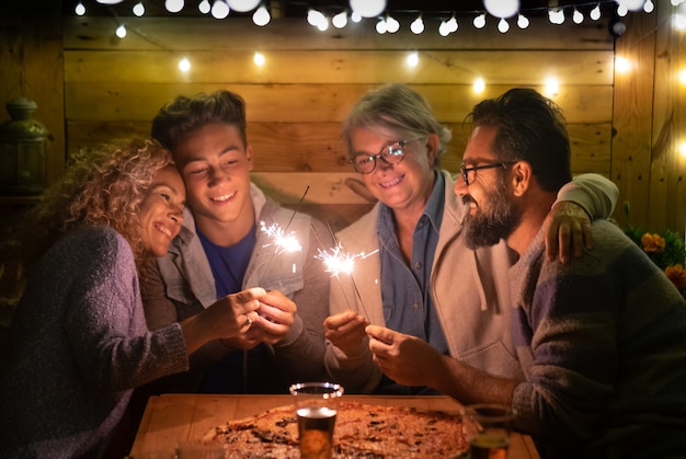 Happy family of four people sparkling wishing a wonderful new year 2020. large pizza on the wooden table. multi generation. concept of happiness and love