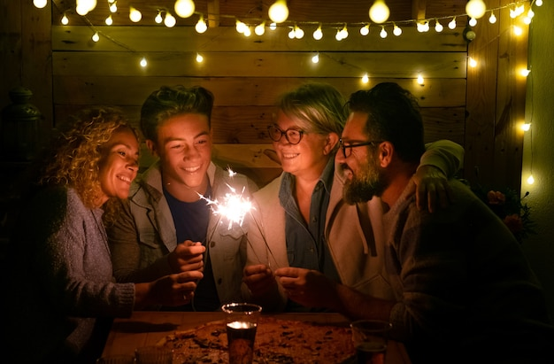 Happy family of four people sparkling wishing a wonderful new year large pizza on the wooden table
