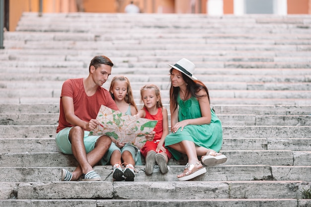 Happy family of four in rome with map