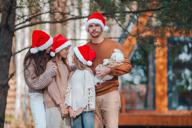 Happy family of four in santa hat enjoying christmas holidays background of their house