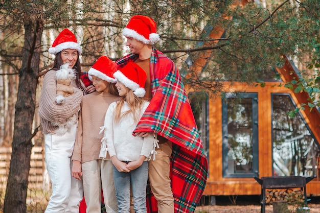 Happy family of four in santa hat enjoying christmas vacation. parent with kids wrapped in a blanket
