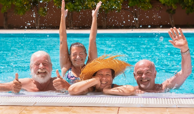 Happy family of four senior people floating in outdoor swimming pool raising splashes of water. they smile relaxed on vacation under the bright sun