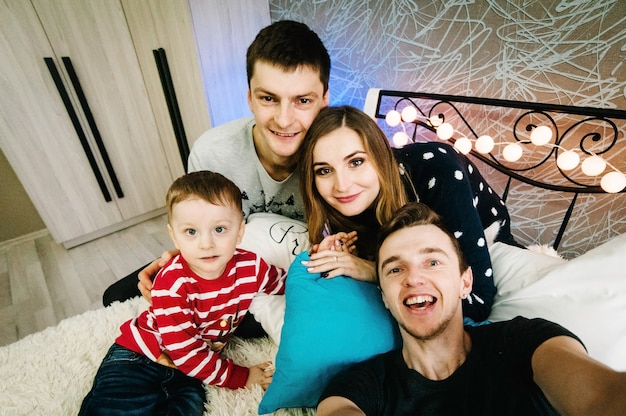 Happy family and friends make selfie on christmas eve in santa claus sweaters, play garland on bed at home. enjoying love, holidays. merry christmas and happy new year.