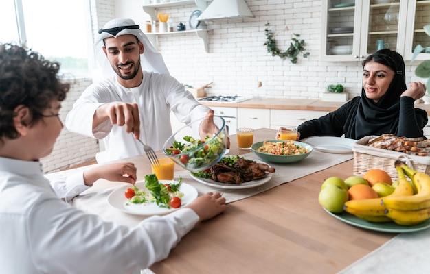アラブ首長国連邦の幸せな家族が一緒に食事をし、建国記念日を祝う