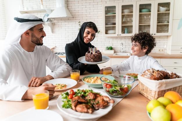 아랍 연합 에미레이트의 행복한 가족이 함께 식사를 하고 국경일을 축하합니다