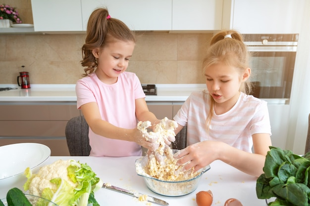Happy family funny kids are preparing the dough, bake cookies in the kitchen. sisters having fun together laughing