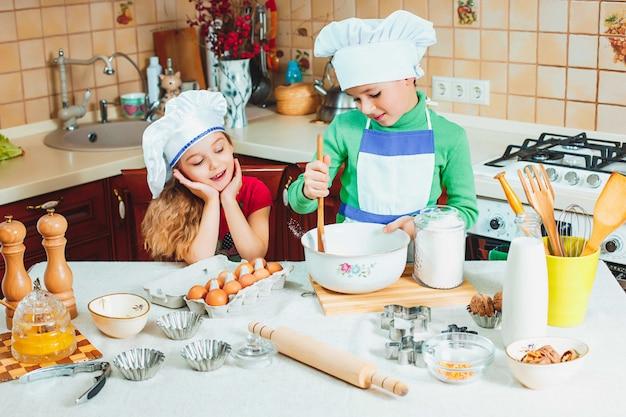 I bambini divertenti della famiglia felice stanno preparando la pasta, cuociono i biscotti nella cucina