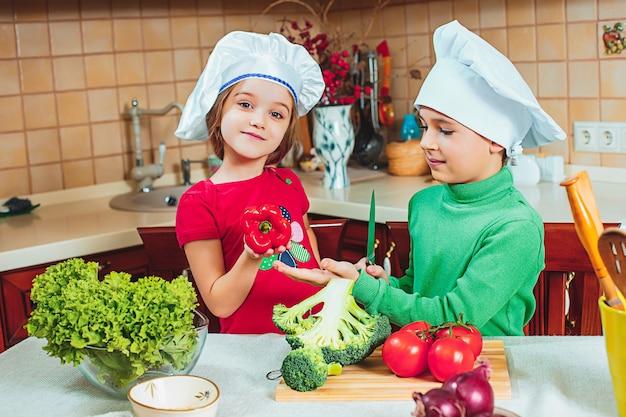 Bambini divertenti famiglia felice stanno preparando un'insalata di verdure fresche in cucina