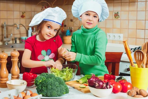 Счастливая семья веселые дети готовят салат из свежих овощей на кухне