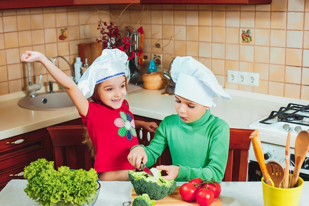Счастливая семья, смешные дети готовят салат из свежих овощей на кухне
