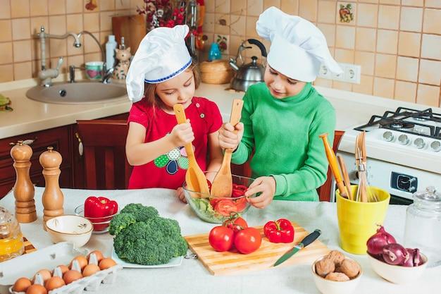 幸せな家族の面白い子供たちが準備している、キッチンで新鮮な野菜サラダ