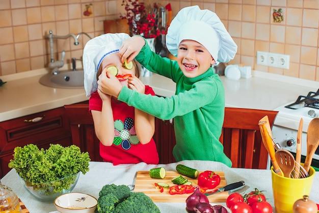 幸せな家族の面白い子供たちは、キッチンで新鮮な野菜のサラダを準備しています