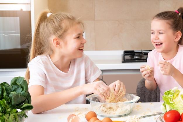 幸せな家族の面白い子供たちは、生地を準備し、キッチンでクッキーを焼きます。一緒に笑って楽しんでいる姉妹