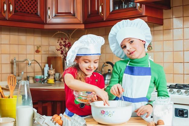 Счастливая семья, веселые дети готовят тесто, пекут печенье на кухне