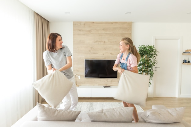 Happy family games, single mother and her child girl are fighting pillows and jumping on couch