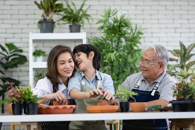 庭で一緒にガーデニングをする幸せな家族、祖父の孫と自然の世話をする女性