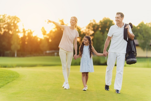 Happy family of golfers walks by sunset lawn.