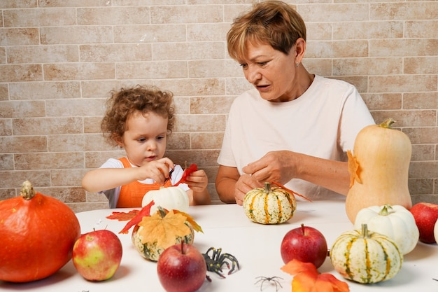 Happy family granddaughter with grandmother making halloween pumpkin at home