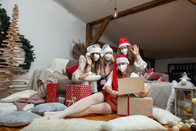 Счастливая семейная группа женщин в рождественских шапках и защитных масках, принимает видеозвонки во время пандемии коронавируса. концепция коронавируса и рождества.