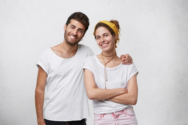 Happy family: handsome bearded male embracing his wife with love who is standing crossed hands and smiling being happy to feel her husband's care. young people hugging isolated over white wall