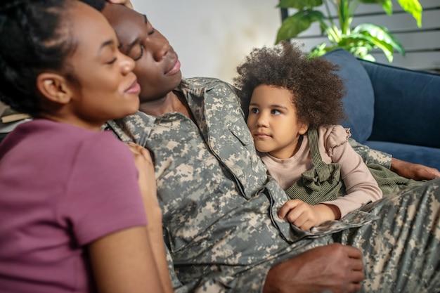 행복한 가족. 행복한 어두운 피부의 군인과 눈을 감고 집에서 소파에 있는 귀여운 딸을 보고 있는 예쁜 여자