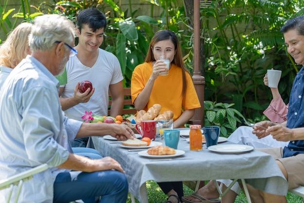 幸せな家族は朝に家の庭で一緒に朝食を食べるのを楽しんでいます